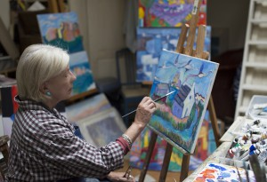 Artist Jean Harvey painting in her studio